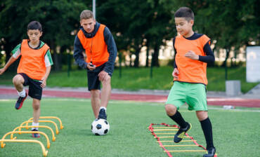 two-school-boys-are-running-ladder-drills-on-the-turf-during-football-summer-camp-intense-soccer-training-with-the-coach.jpg